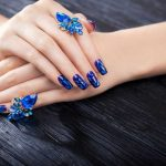 Shattered glass blue manicure on black background